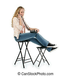 Woman Phone Casual - Young woman sitting on stool speaking...