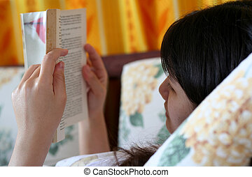 Reading A Book - An asian girl lying on the sofa reading a...