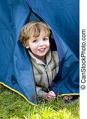 First Time Camping - A young boy emerges from a tent on a...