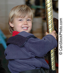 Child on Carousel - My son on a moving carousel, smiling.