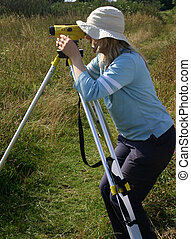 Female surveyor - Girl doing archaeological field surveying...