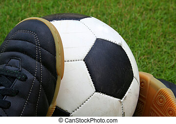 A soccer ball and a pair of shoes - A worn-out soccer ball...