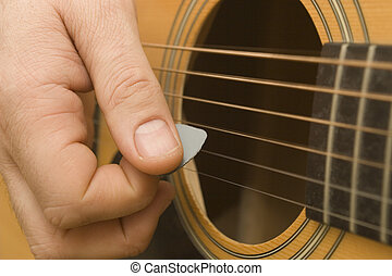 Playing Guitar - Close up of a guitarist playing a guitar...