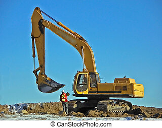 backhoe - a backhoe pauses for instructions