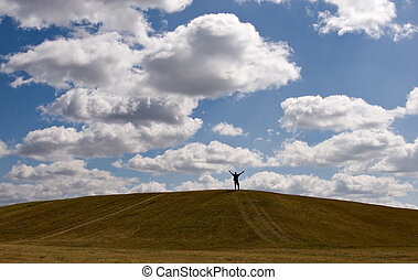 Carefree - Man with outstreched arms on top of small hill
