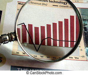 Business Focus - A magnifying glass focusing on a chart in...
