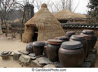 Kimchi (pickled cabbage) pots outside at straw tent at Suwon...