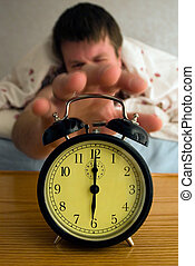 Rise & Shine! - Tired man reaching for his alarm clock at...