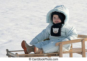 On my sled - A baby sitting on the sled
