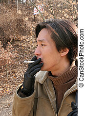 Asian man smoking a cigarette