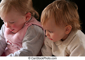 Friends - A portrait of little babies against a black...