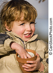 Flower Pots - A young boy plays with two flower pots in a...