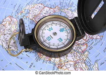 compass and map - Open compass resting on a map of the world...
