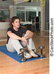 Man with dumbbels on exercise mat - Man with dumbbels...