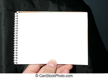 holding blank spiral notebook on abstract background