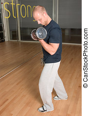 Biceps curls - Handsome blond man doing biceps curls in the...