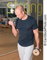 Handsome man doing biceps curls - Handsome blond man doing...