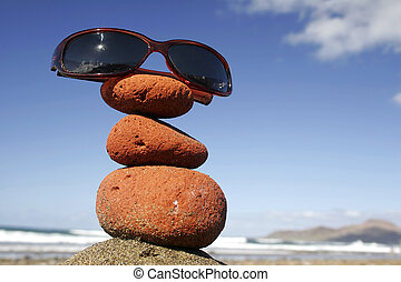 Sunglasses Stack - Sunglasses on stone stack by the beach