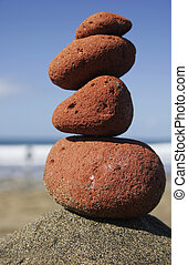 Red Stone Stack - Red sandstone pebbles in a stack on the...
