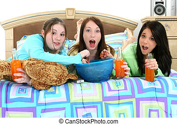 Teen Slumber Party - Three teen girls eating and watching...