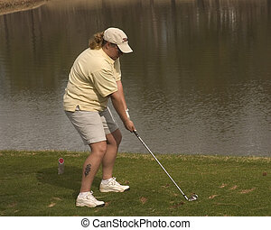 Tee Off Over Water - Woman golfer teeing off over water