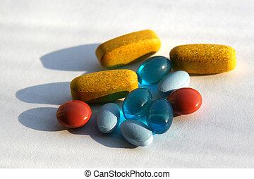 Assortment of Pills - yellow, red, blue and light blue pills...