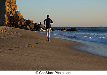 Beach Runner - Man running on the shore of Pointe Dume beach...