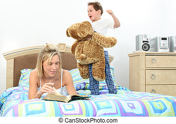 Mother Son Family - Mom reading book to son while he plays...
