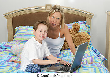 Mom Son Computer - Mother and son with laptop sitting in...
