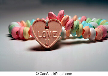 Love U 6 - Candy necklace with Love u pendant propped in...