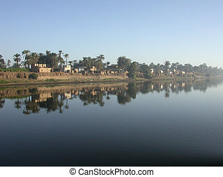 Village on the Nile - Small village reflecting into the...