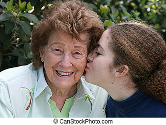 Girl Kisses Grandmother - A girl giving her grandmother a...