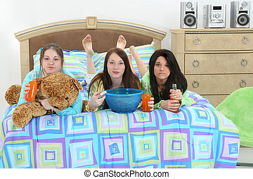 Slumber Party - Three teen girls with snacks, drinks and...