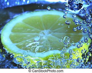 Lemon drink - Water drops falling onto lemon slice