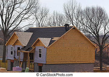 Roofer on new house - Roofer applying tar paper to roof of...