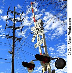 Railroad crossing and telephone pole in blue sky and clouds