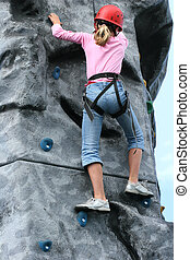Endurance Training - Young girl climbing on a training rock...
