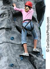 Endurance Training - Young girl climbing on a training rock...