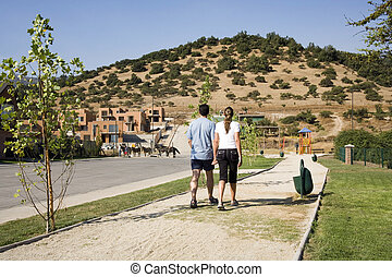 Couple walking in suburban development on summer day