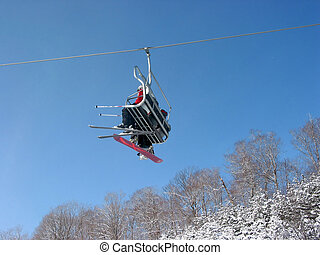 Ski chairlift - Skiers and snowboarders on a chairlift, snow...