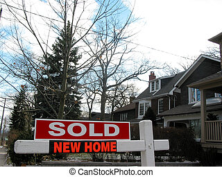 Sold new home - Sold sign next to a newly built house