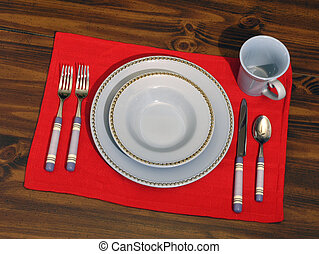 Place Setting - Dining place setting on a red mat and wood...