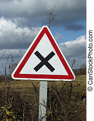 crossroads sign in the hedgerow