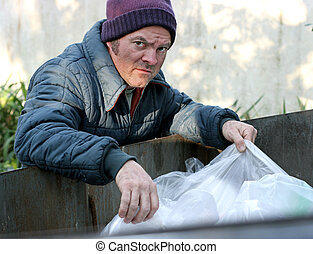 Homeless Man - Roots In Dumpster - A homeless man rooting in...
