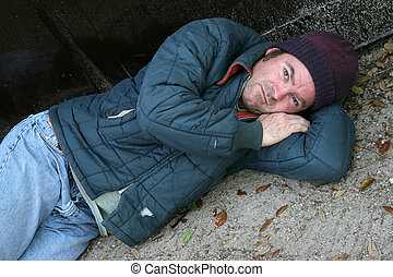 Homeless Man - Society's Problem - A homeless man lying on...
