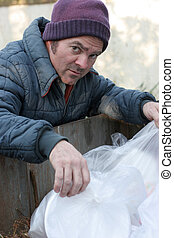 Homeless Man - Digging In Dumpster - A homeless man looking...
