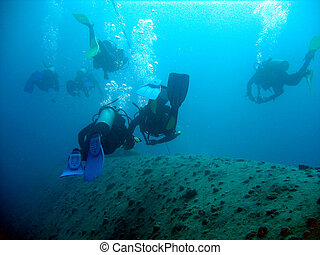 Exploring the wreck - Scuba divers exploring the wreck of...