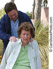 Son Comforting Mother - A grown son laying his hands on his...