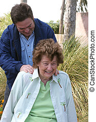 Massage In The Garden - A pretty senior woman receiving a...