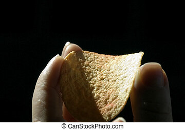 Isolated Hand holding a Chip with black background